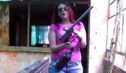 Red haired sweetie looks so serious with the gun in her hands